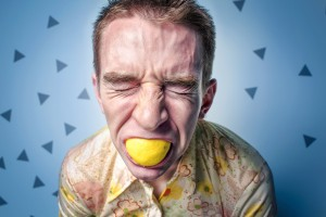 man sucking on lemon with sour face