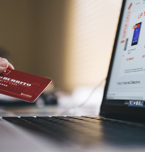 a woman's hand holding a credit card next to a laptop