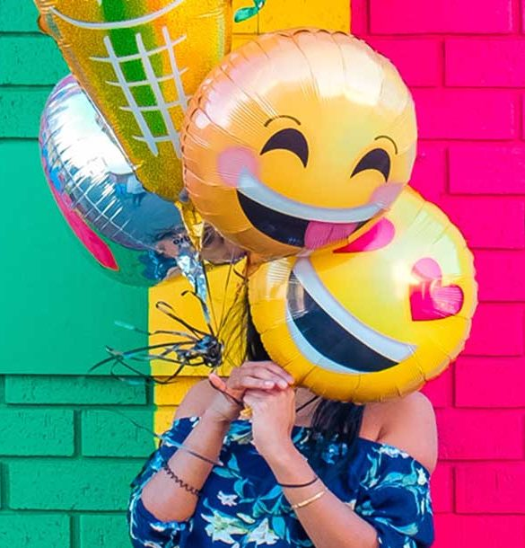 a woman holding emoji balloons in front of her face